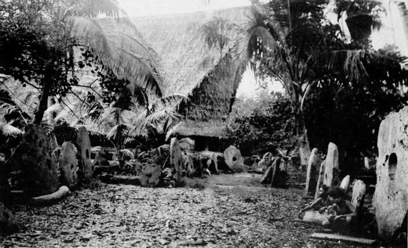 Photograph on a postcard, from the period of Japan's South Seas Mandate, showing a large men's house and rows of stone money in a village on Yap.