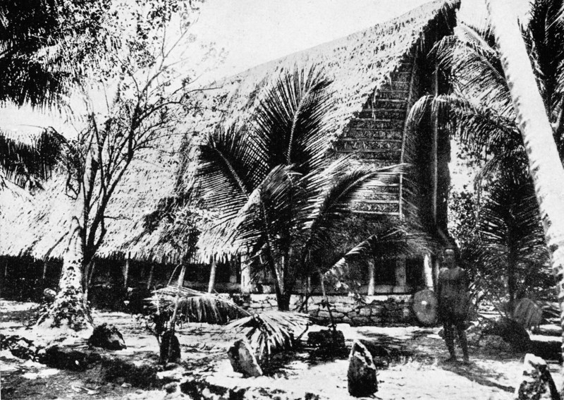 A Yapese man stands in front of a large men's house in Tomil, 1921 (Junius B. Wood)