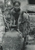 Palau:  A woman with a small bowl bending over a large clay urn (Augustin Kramer, 1910)