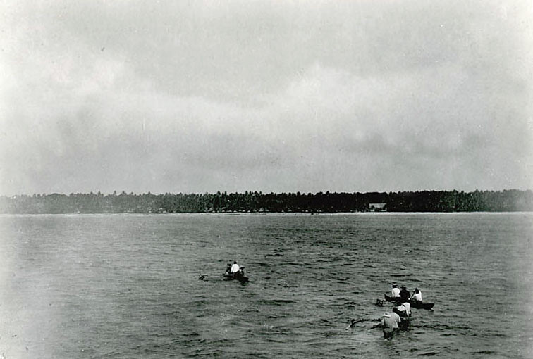 Kosrae, 1899:  Photograph by Henry Clifford Fassett showing three outrigger canoes being rowed towards a coastal village