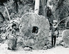 Yap, 1962:  Photograph by Roy H. Goss showing a young girl and Chief Anghel Gargog standing on either side of a piece of stone  money