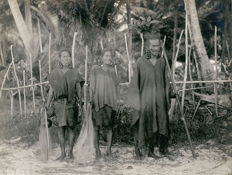 Chuuk, 1899:  Photograph by Henry Clifford Fassett showing two women in traditional asttire with the high chief of the Mual District on Moen