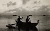 Two Mariana Islanders in an outrigger canoe, with Japanese fishing boats anchored off Saipan in the background, circa 1930