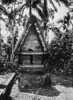 On Koror, a Palauan girl stands beside a shrine in the shape of a miniature men's house (Junius B. Wood, 1921)