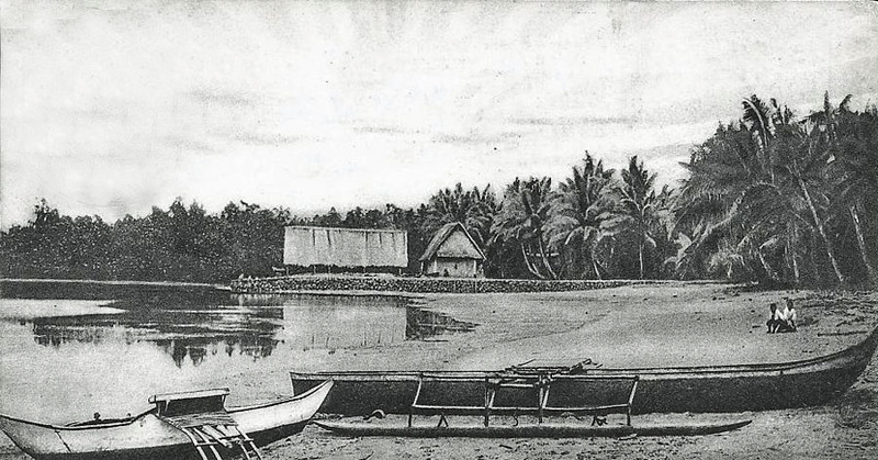 Kosrae, about 1920:  Two buildings, canoes, and boys at a coastal village