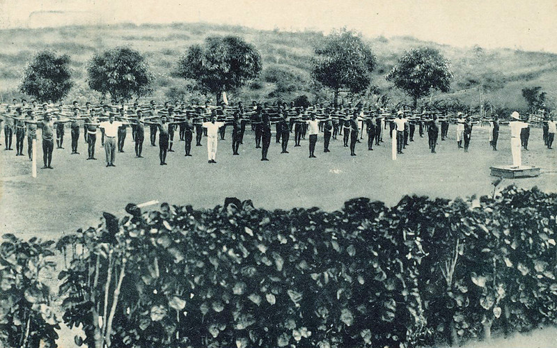 Postcard photograph from the period of Japan's South Seas Mandate, showing Yapese men being led in an exercise regimen inside a plant-walled field