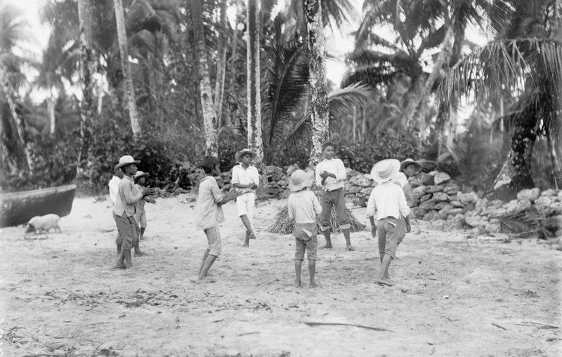 Kosrae, 1899:  Henry Clifford Fassett photograph of boys playing ankle ball on a beach near Port Lottin; pig and canoe prow on the left