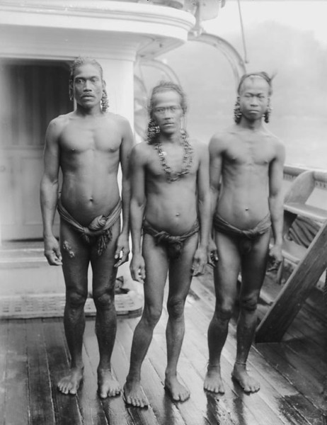 Chuuk, 1899:  Photograph by Henry clifford Fassett of three Chuukese men in loincloths on the deck of a modern steamship