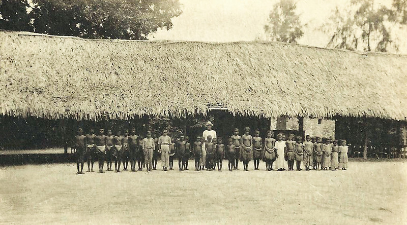 From the period of Japan's South Seas Mandate, on Angaur, a group of school children and their teacher pose in front of their school
