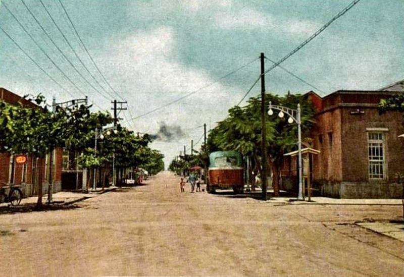 A bus and a few strollers on an otherwise quiet Suzuran Street, Tinian, circa 1935