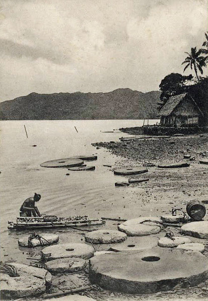 Remarkable postcard photograph from the period of German rule, showing several pieces of stone money, apparently recently brought back, lying on a beach