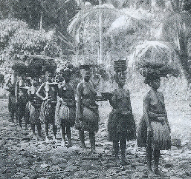 A group of Palauan women carrying food for a feast on their heads (Augustin Kramer, 1909)