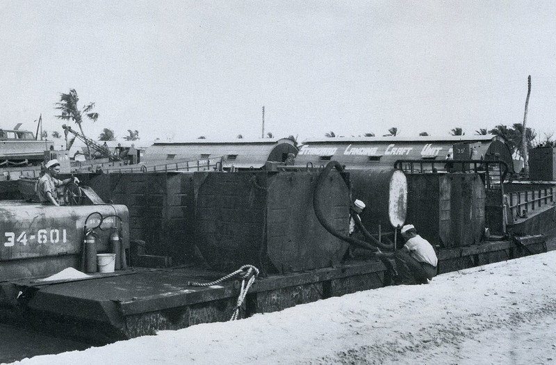 Refuleing from a small self-propelled fuel barge on Ulithi; 'Standard Landing Craft Unit' Quonset huts in the background (U.S. Navy, National Archives)