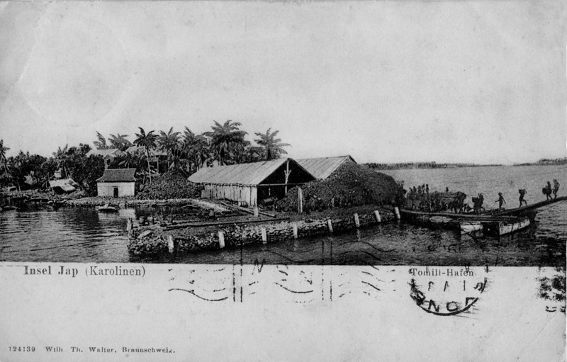 "This is the front of a postcard sent from Yap to County Kerry, Ireland, on October 14, 1908.  The German caption says:  ""Yap Island (Carolines) Tomil Harbor.""  According to Stan Retogral and Eric Metzgar, this is a view of Colonia, and the dock and warehouses pictured here were situated just beyond the present-day Yap Legislature building, which sits on the rise of land behind the warehouses here.  Eric says this appears to him to be a view of the dock, looking north, with Tarang (O'Keefe's Island) in the distance on the right.  There has been extensive landfilling, both sideways and lengthwise, in the area since this photo was taken.  Stan says that today the Yap Fisheries are located on landfill to the left and the commercial port on landfill to the right, overlooking Tomil.  It looks like the men on the right are carrying goods to and from a vessel out of view, probably the same one the photographer was on.  Are those stacks of copra?  The lower caption says: ""124139 Wilh. Th. Walter, Braunschweig,"" the photo/card number and the photographer/printing company in Braunschweig.  For those who want a closer look, there are several larger photo sizes available (click on the right side of the photo).  For a modern view of this area, see Barry Basel's photo taken in April 2004 from the cockpit of a Coast Guard C130 transport plane."