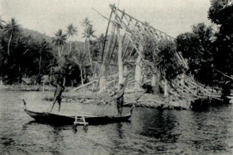 Photograph on an old postcard, from the period of the Japanese Pacific Mandate, showing two men on a canoe in front of the framework of a house being built in what appears to be Chamorro Bay