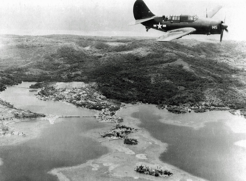 An SB2C Helldiver bomber flying over Colonia, Yap, on August 28, 1945, a little over a week after Japan's surrender (U.S. Department of Defense, Marine Corps, photograph)