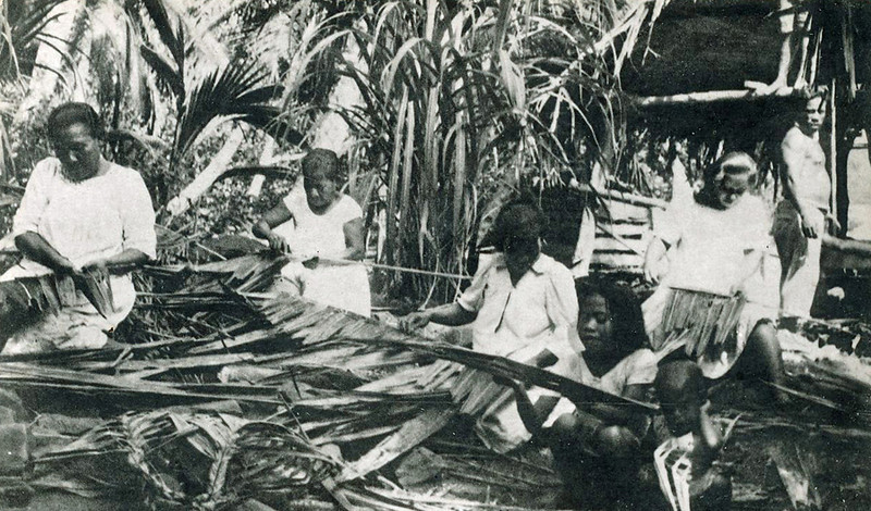Pohnpeian women weave palm branch leaves, while a man looks on (photo from the period of Japan's South Seas Mandate)