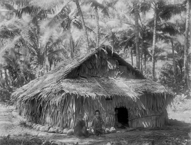 Chuuk, 1899:  Henry Glifford Fassett photograph of three children sitting in front and in the doorway of a thatch house on Moen