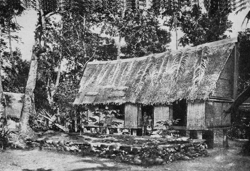On Koror, residents in front of a Palauan house, abutting a raised stone platform, 1921 (Junius B. Wood)