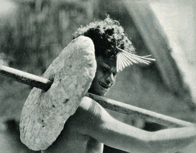 "From ""The Illustrated London News"" of 24 April 1937:  ""Carrying his stone money on a pole over his shoulder, a native of Yap, with a mangrove-wood comb (the sign of high rank) in his hair."""
