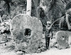 Yap, 1962:  Photograph by Roy Goss showing Chief Anghel Gargog standing between two pieces of stone money