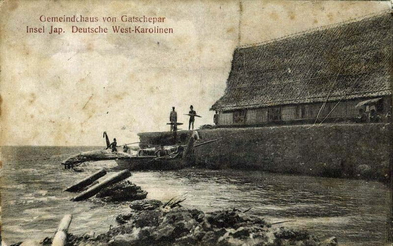 "Photograph from the first decade of the 1900s, showing men and a large canoe outside the men's house in Gatchepar on Yap.  The German caption reads ""Gatchepar Community House, Yap Island, German West Carolines.""  Gatchepar is the village in Gagil municipality on Yap from which the paramount chief of Yap traditionally comes."