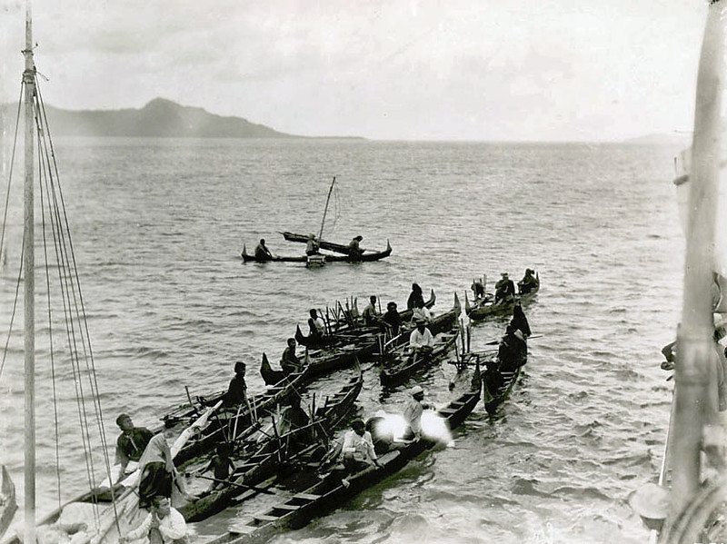 Chuuk, 1899:  Photograph by Henry Clifford Fassett showing Chuukese men in several outrigger canoes coming alongside a large streamship in the Chuuk Lagoon; Faichuk in the background