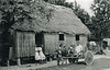 Family and ox-cart outside a house on Saipan, about 1920