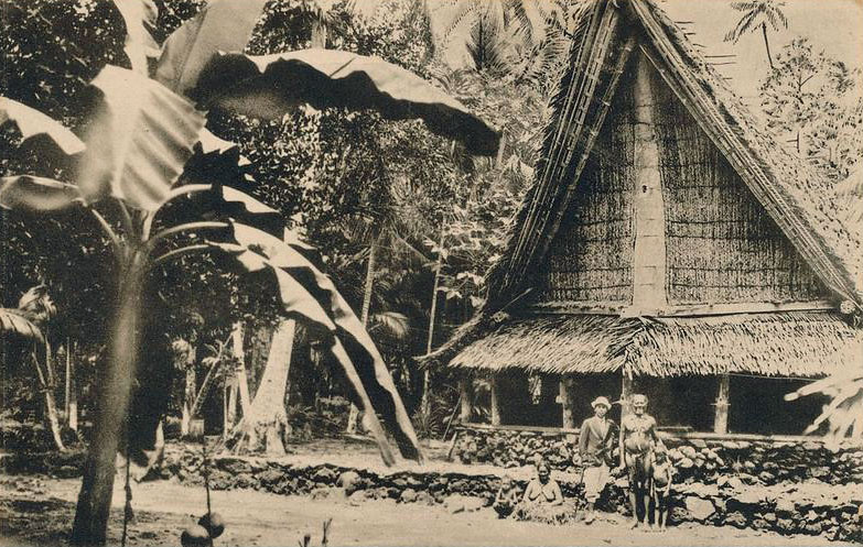 Another postcard photograph from the period of Japan's South Seas Mandate,  This one shows a Japanese man in fashionable dress, standing with a Yapese woman, man, and two boys, in front of a well-maintained Yapese house.