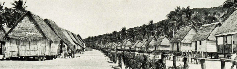 Thatch-roofed houses lining the main road through the principal village on Rota, 1921 (photograph by Junius B. Wood)
