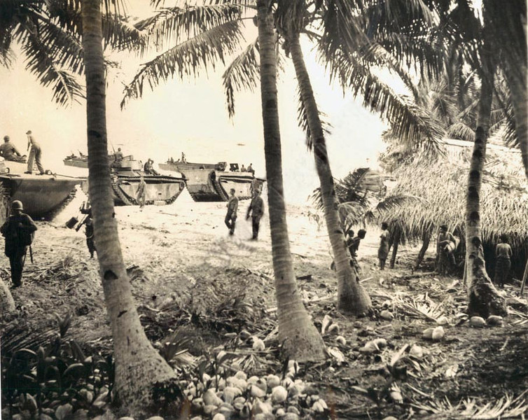Disembarking from amphibian tractors, Americans of the Eighty-First Division go ashore on the beach of Mogmog during their September 20, 1944, invasion of the Ulithi Atoll; islanders look on (Associated Press photograph)
