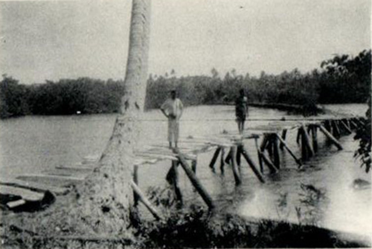 Photograph on an old postcard, from the period of the Japanese South Seas Mandate, showing two men on a short wooden causeway