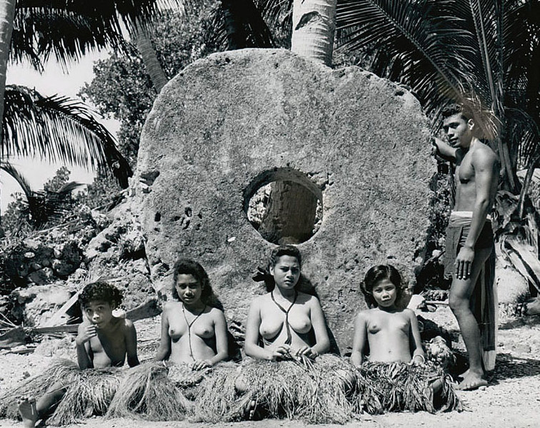 Yap, 1962:  Photograph by Roy H. Goss showing four young women and a young man framing a large piece of stone money