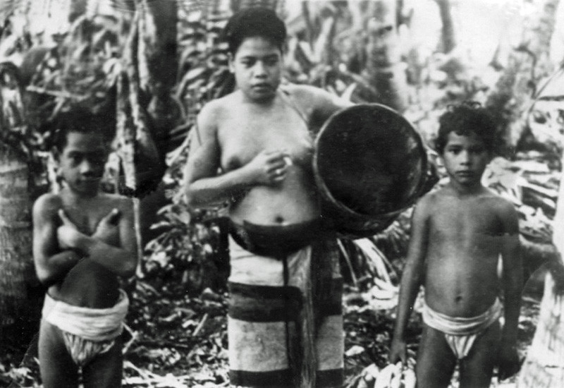 Photograph of two boys and a woman (smoking a cigarette and carrying a basket) taken by a U.S. soldier on Ulithi in 1944.