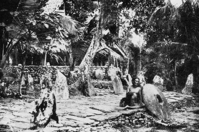 In front of a men's house on raised stone platforms in Tomil on Yap, a man leans against a raised stone slab beside a piece of stone money (Junius B. Wood, 1921)