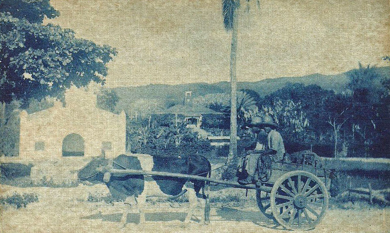 A Japanese-era photograph of Saipan, showing two men and an oxcart in the foreground.  To the left is a Catholic mission church; in the center rear is the building housing the Japanese military headquarters on the island.