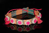 "A colorful ""shell flower"" woven belt, made in the Marshall Islands, and bought in an island craft shop on Majuro in the summer of 1969.  The flower-ornamented band is 1-1/2 inches wide and 20 inches long.  The pink and yellow tassled-tie straps are each 8 inches long."