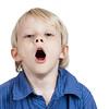 Tired cute young boy yawning.