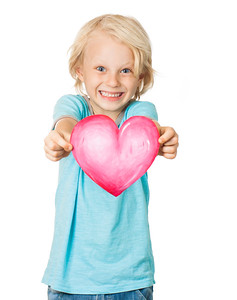 Cute young smiling boy holding love heart