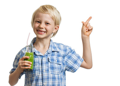 Cute boy holding green smoothie and pointing