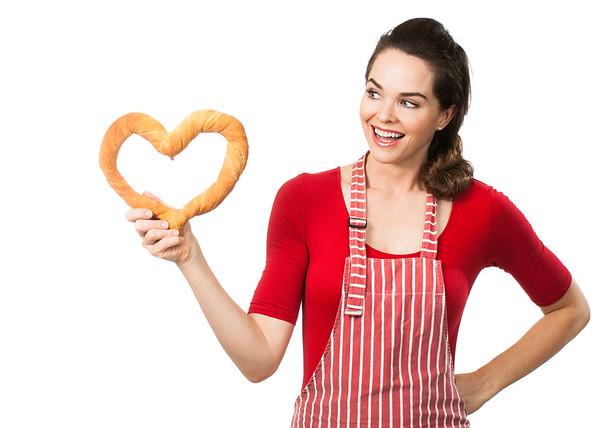 Beautiful woman holding a bread love heart.
