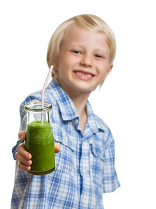 Cute boy holding green smoothie or juice