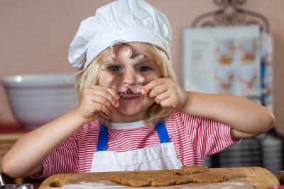 Cute smiling boy peeking through cookie cutter