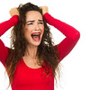A very frustrated and angry and upset woman is screaming out loud and pulling her hair. Isolated on white.