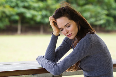 Sad and upset woman sitting outdoors