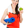 Fit woman with yoga mat and apple