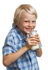 Happy cute boy drinking bottle of milk.