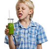 Boy poking tongue out at green smoothie