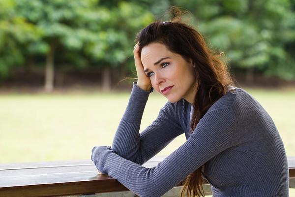 Sad depressed woman sitting outdoors