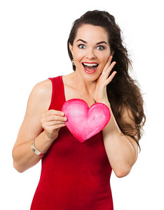 Beautiful surprised woman holding a love heart